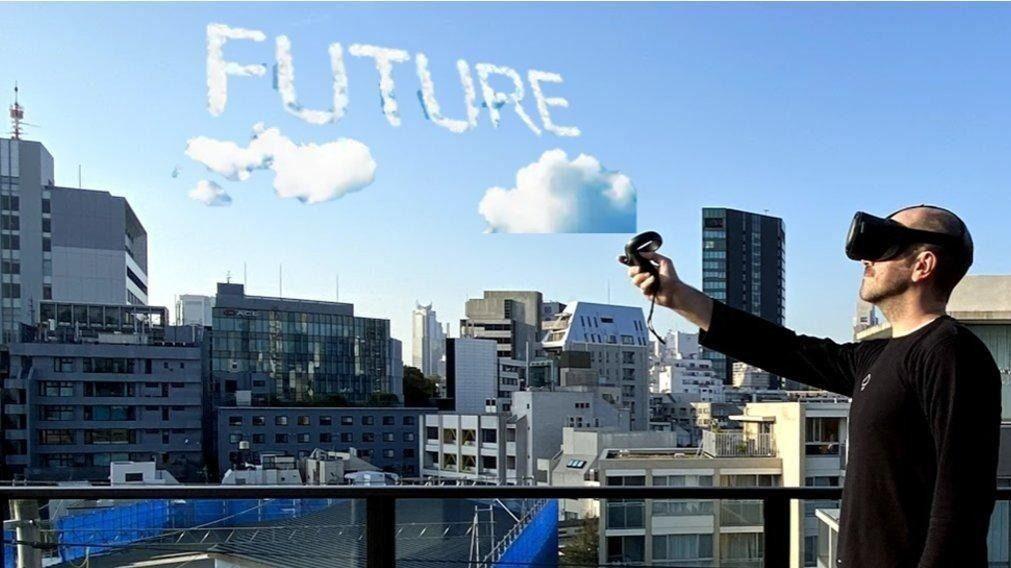VRのゴーグルを装着した人が、空に「FUTURE」の文字を雲で描いているイメージ写真